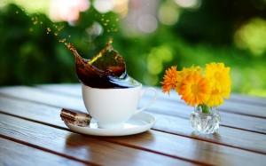 coffee_splash_in_cup_on_wooden_table-wide